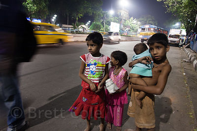 A group of children panhandle for money at night on a busy road in Kumartoli, Kolkata, India.