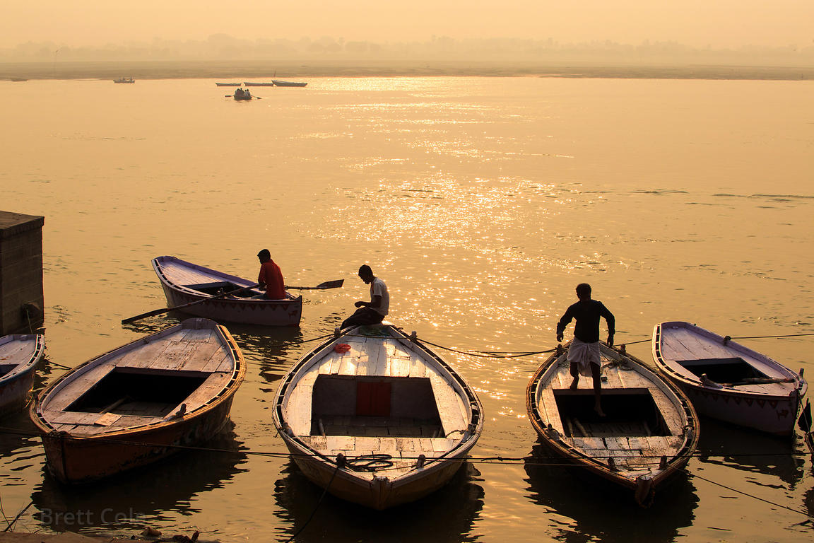 Boatmen in golden light at sunrise on the Ganges River, Prayag Ghat, Varanasi, India