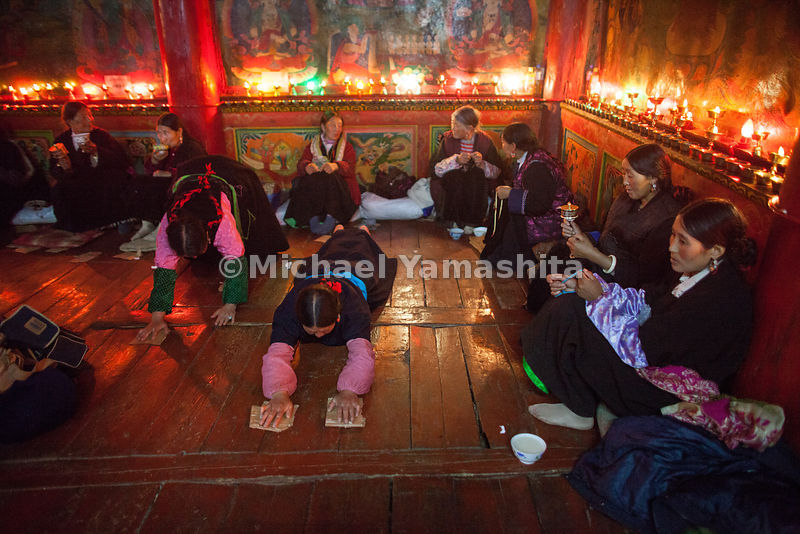 Local women share in the celebration at Garthar Monastery by performing Shak Tsal, turning prayer wheels and fingering prayer...