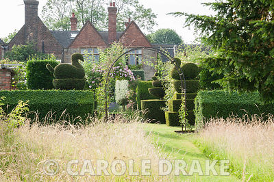 Grass paths are mown through the meadow, leading toward the formal garden with yew hedges and topiary near the house. Felley ...