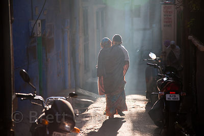 A woman walks down an alley in early morning light, Jodhpur, Rajasthan, India