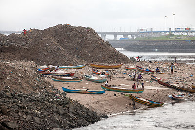 Fishing boats amid piles of garbage on the shore of Mahim Bay (Arabian Sea), Mahim, Mumbia, India.