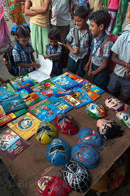 Schoolchildren look at halloween-type masks for sale at a market in the Kokri Agar slum, Mumbai, India.