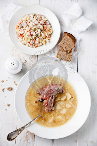 Russian traditional salad olivier and Pea soup with bread and smoked ribs