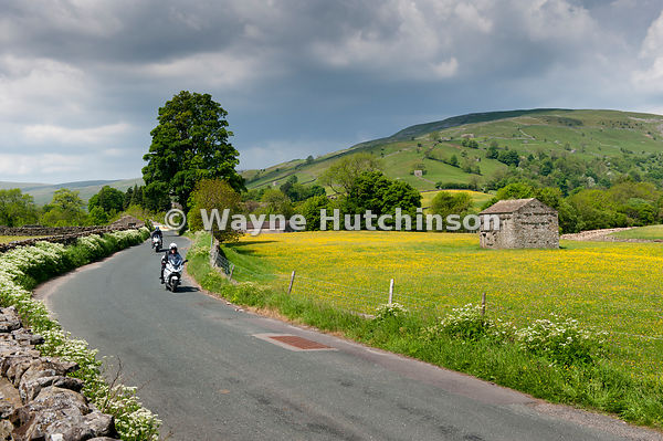 Motorbikes on a narrow rural road in Swaledale, North Yorkshire, UK.