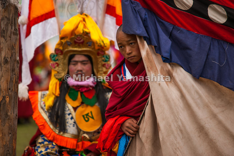 Waiting in the wings, a monk in warrior costume awaits his cue for the call to battle at the Ling Gesar reenactment, which is...