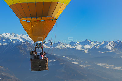 Passengers taking photographs of the dawn landscape on a hot air balloon in flight over the Aosta Valley region of the northe...