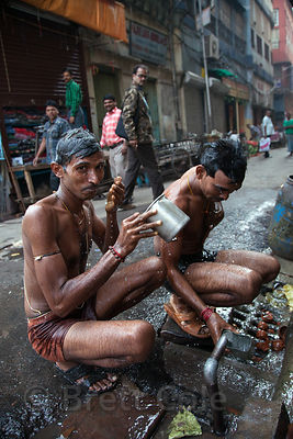 Men bathe at a public water spigot in Shyambazar, Kolkata, India