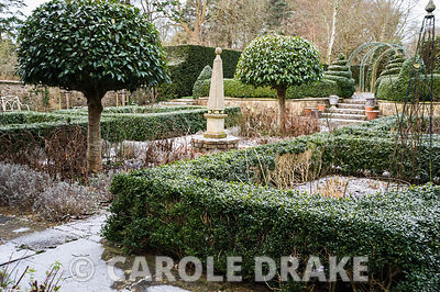 Courtyard garden featuring beds enclosed by clipped box hedges, standard Portugese laurels and a central stone obelisk.