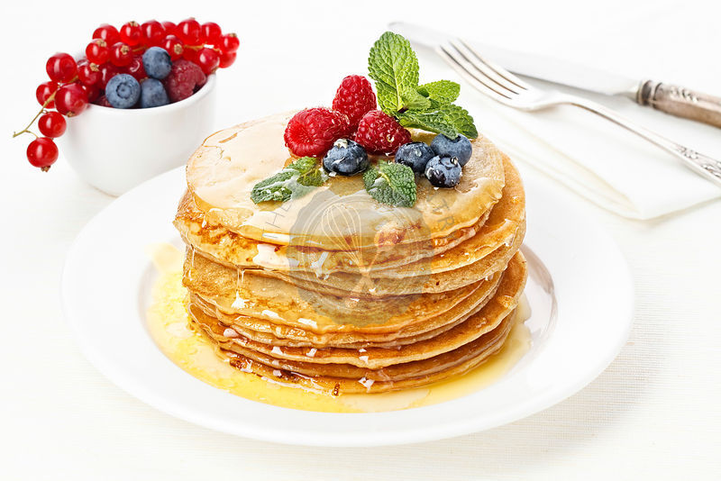 Pile of delicious handmade pancakes topped with honey, raspberries and bilberries