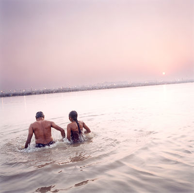 A pilgrim and his wife get ready to immerse themselves in the Ganges as an act of religious purification