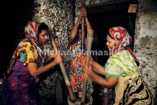 Dressed in kanga cloth, Famao women from the Farouk family pound corn for cornmeal to make bread.