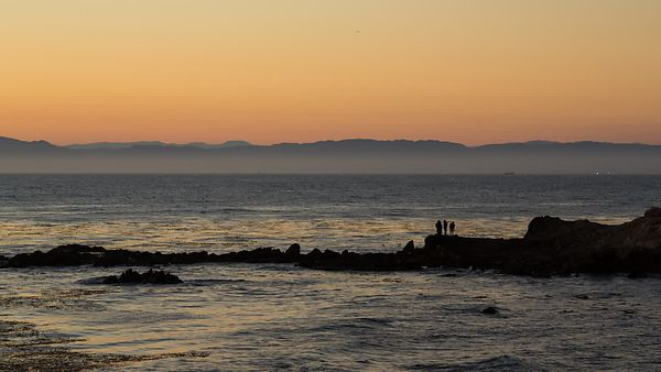 Wide Shot: Friends Silouhetted On the Rocks Of A Palos Verdes Sunset