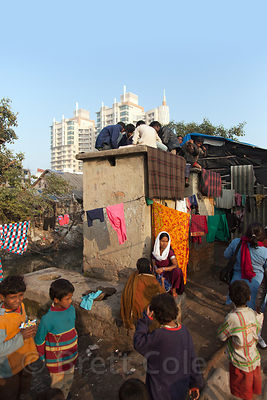 People play cards atop a house in a slum area in Ward 66, Muchipara, Kolkata, India. Many people in the community make sandals.