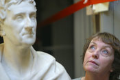 A visitor to the Sir John Soanes Museum, London looking at the exhibits next to a bust of Sir John Soanes