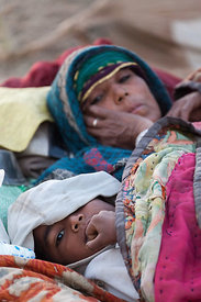 A boy sleeps on a cot with his mother at the Pushkar Camel Mela, Pushkar, India.