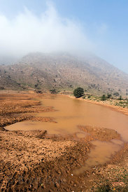 Small muddy pond in the desert, Kharekhari village, Rajasthan, India