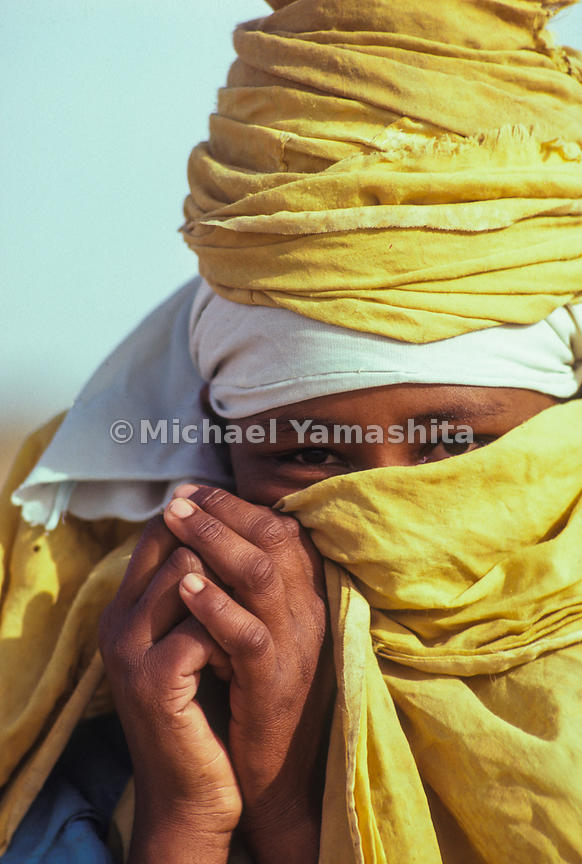 A Sudanese person wears a traditional robe to protect their face from the sand.