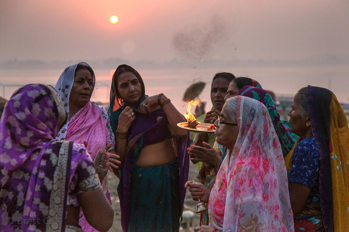 A group of women carry out a prayer on the Ganges River, Assi Ghat, Varanasi, India
