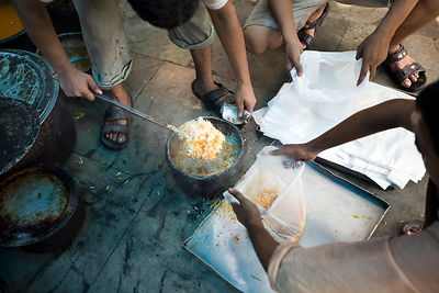 India - Delhi - Men spoon biryani into plastic bags for delivery at Babu Shahi Bawarchi
