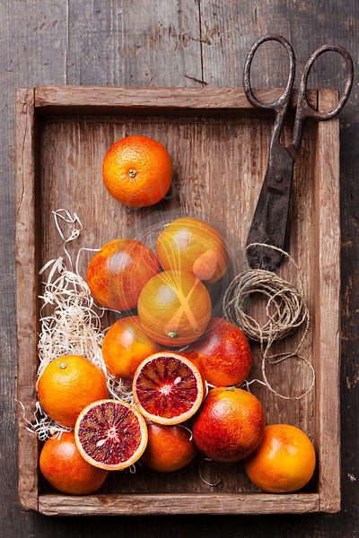 Ripe red oranges on textured wooden background