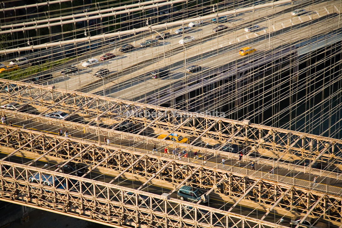 The maze of cars and pedestrians traversing the Brooklyn Bridge crosses over the FDR Drive, which passes underneath its Manha...