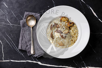 Risotto with porcini mushroom on plate on dark marble table background