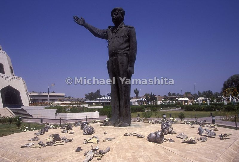 Battle statue of Saddam stands amidst pieces of U.S. missle. Baghdad, Iraq.
