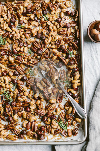 Spicy candied nuts are flavored with fresh rosemary leaves and photographed from the top view.