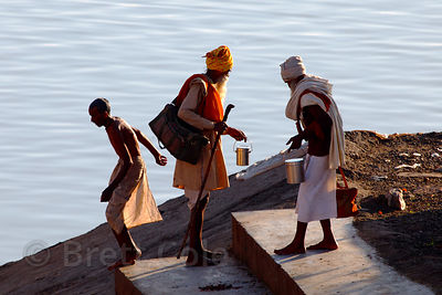 Elderly sadhus (holy men) walk the steps of a small temple in the lake at Pushkar, Rajasthan, India