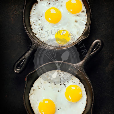 Pans with fried eggs on old metal background, top view. Food. Breakfast. Healthy food.