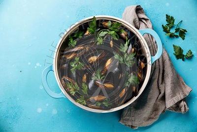 Mussels Clams in cooking pan with parsley on blue background