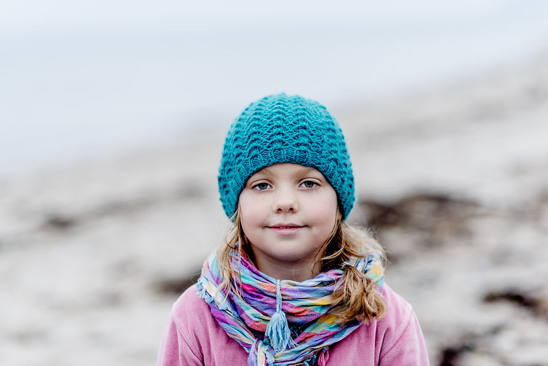 Little Danish girl in a blue hat at the beach in autumn 10