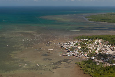 Aerial view of highly populated region of Puerto Princesa coastline with outrigger boats and houses, Philippines, April 2010