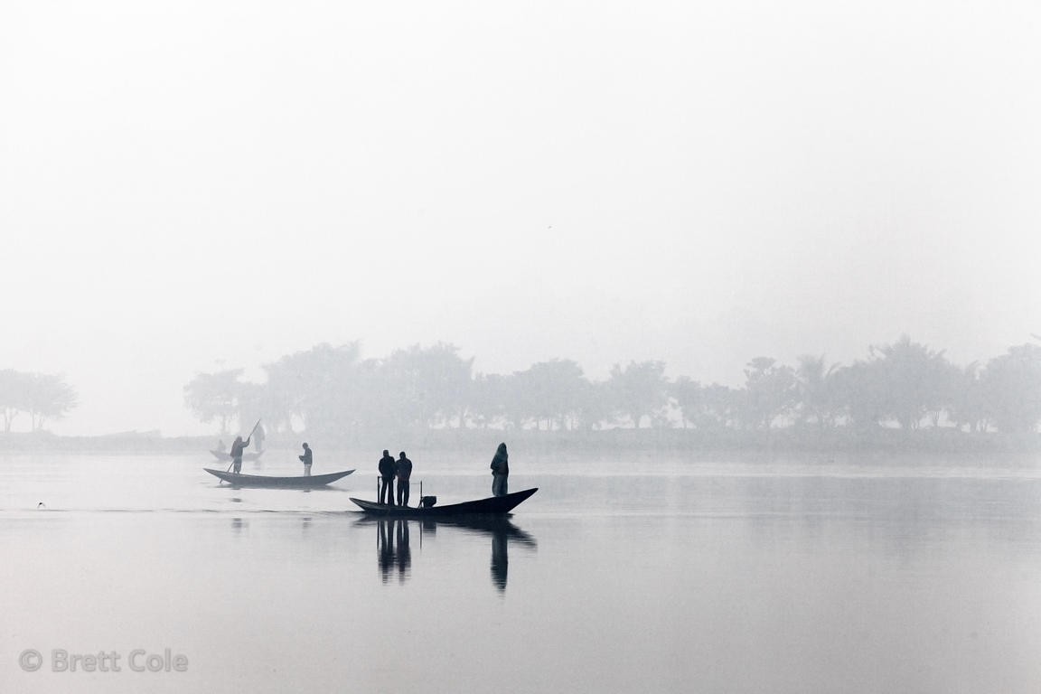 Fisherman on open water on a foggy winter morning in the East Kolkata Wetlands, Kolkata, India.