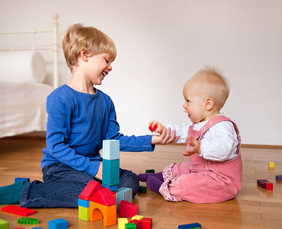 boy and baby with toy building blocks