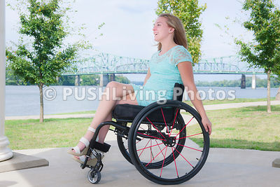 Young woman using a wheelchair in a riverside park