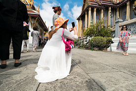 Tourists pose for selfies at the Grand Palace in Bangkok, Thailand.