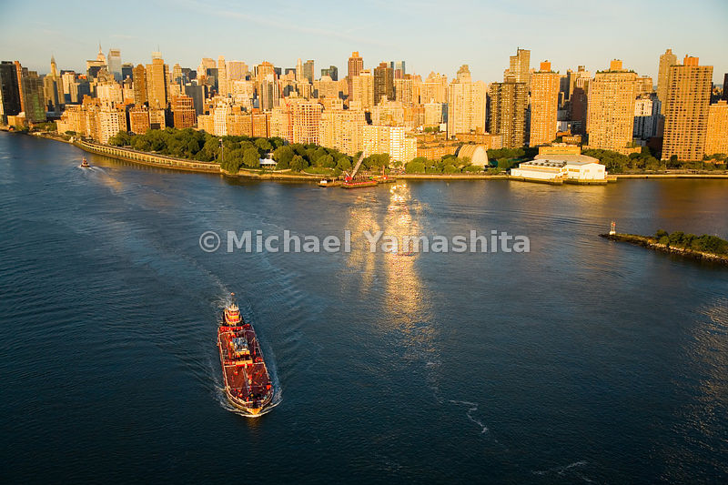 Barges in the East River get sunrise views of Carl Schurz Park and the Upper East Side.  Manhattan, New York City.