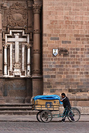 A bread delivery man pushes his cart past a church in Cusco, Peru