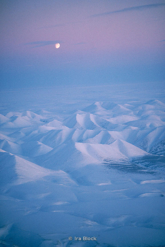 Moon over the Brooks mountain range in Alaska.