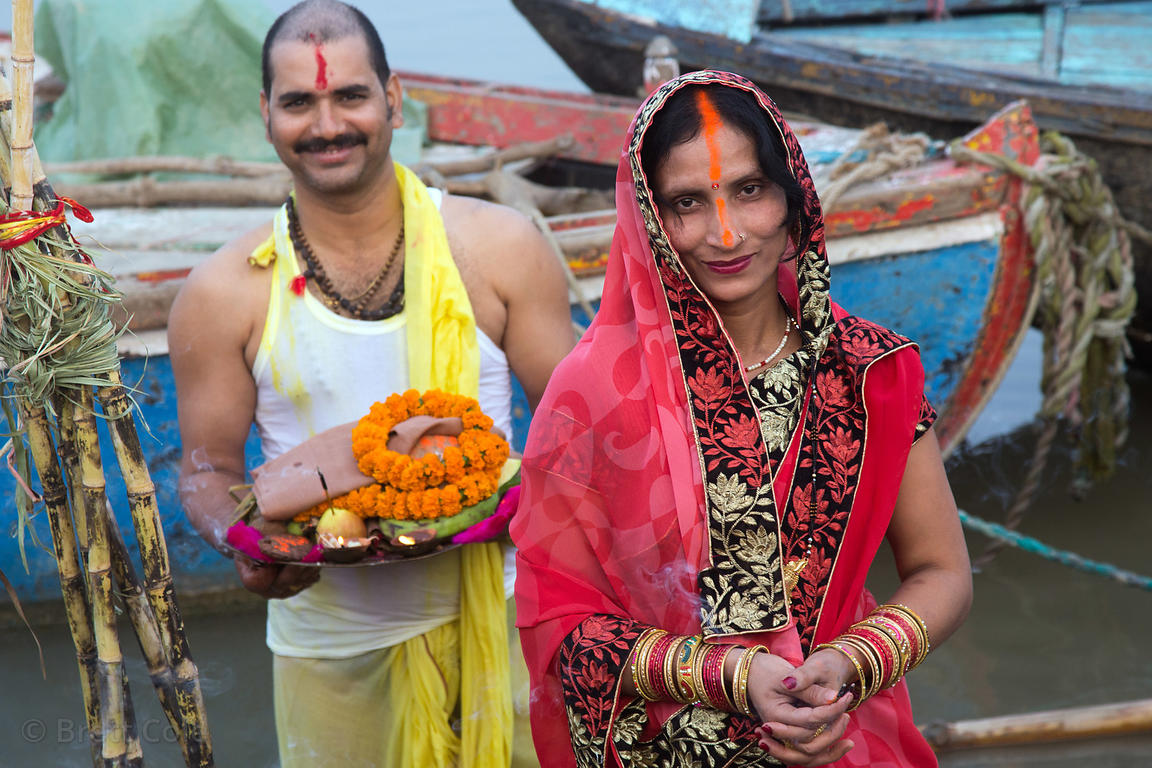A couple makes offerings on the Ganges River during Chhath Puja, Varanasi, India. Chhath Puja is a devotion to the Sun God Su...