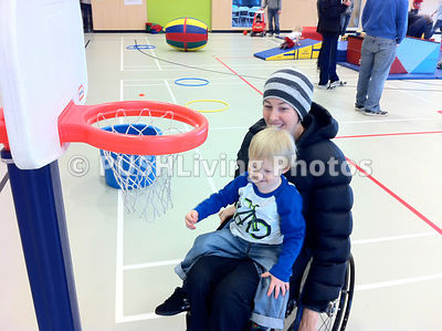Mother in a wheelchair playing basketball with her young child