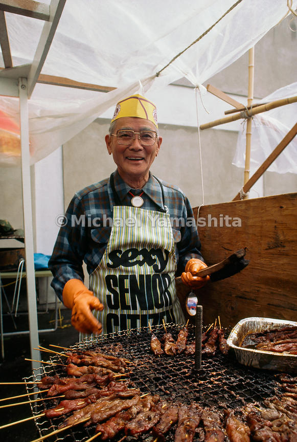 At ease in two cultures, Hisao Inouye tends a grill laden with teriyaki during San Francisco's Cherry Blossom Festival. Overc...