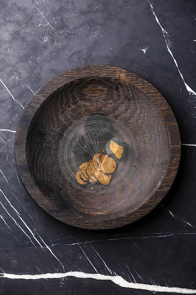 Black truffle on wooden plate on dark marble background