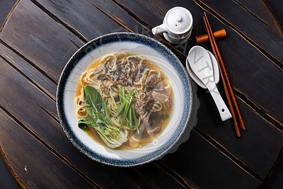 Ramen asian noodle in broth with Beef and Oyster mushrooms in bowl on dark wooden background