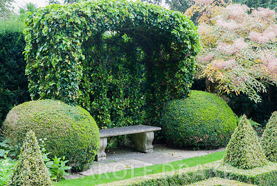 Ivy covered port-cullis shaped gazebo at the end of the Knot Garden of clipped box. Bourton House, Bourton-on-the-Hill, Moret...