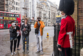 Teenage students at a photo workshop taking photos of a Queen's Guard in London, UK.