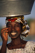 Peul woman, with characteristic mouth tattoo carrying water, Djenné, Mali
