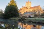 Wells Cathedral lit golden by dawn sunlight on a November morning